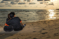 Swain sitting together on the beach and watching sunset, romance Stock Images