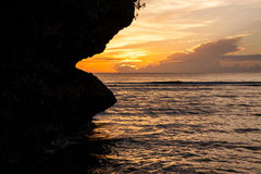 Swallow the sun. Silhouette of Face-shaped rock at sunset Stock Photo