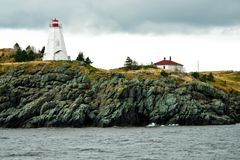 Swallowtail Lighthouse. The Swallowtail Lighthouse stands majestically on top of a cliff on a grey, overcast day. Grand Manan Island, New Brunswick, Canada royalty free stock photography