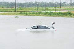 Swamp car flood. Sedan car swamped by flood water in East Houston, Texas, US by Harvey Tropical Storm. Submerged car on deep heavy high water road. Disaster Stock Photo