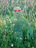 Swamp Monster Surrounded by Wildflowers. A swamp monster surrounded by purple and white wildflowers.  The monster is green with red eyes stock photo