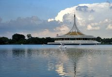 Swan boat under beautiful sky and reflection of Ratchamangkala Pavilion in lake of  The Suan Luang RAMA IX Public Park. Ratchamangkala Pavilion In The Suan Luang Stock Photo