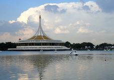Swan boat under beautiful sky and reflection of Ratchamangkala Pavilion in lake of  The Suan Luang RAMA IX Public Park. Ratchamangkala Pavilion In The Suan Luang Stock Photography