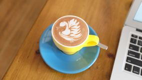 Swan Design in Cappuccino in Yellow Mug Royalty Free Stock Images