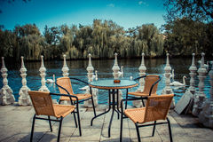 Swan Lake. Table with chairs on the banks of the waters of a lake with white swans Stock Image