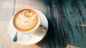Swan Latte art in the white cup on wooden table  with sunlight for background Royalty Free Stock Photos