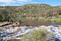 Swan Valley Bell Rapids: Western Australia. Bell Rapids white waters and treed riverbank with granite rock and treed riverbanks under a blue sky with clouds in Royalty Free Stock Image