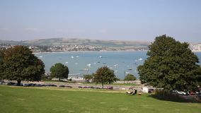 Swanage Dorset England UK with sea and coast PAN view. Swanage Dorset England UK with town sea and coast on a beautiful blue sky summer day stock footage