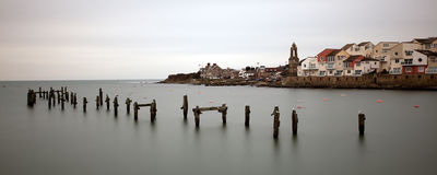 Swanage town coastline. Wide angle view of Swanage town coastline viewed over sea with wooden breakwater posts in foreground, Dorset, England Royalty Free Stock Images
