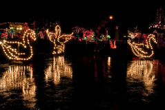 Swans in Christmas Lights At Night. This holiday image show swans in Christmas lights at night with the light reflecting off an icy pond.  Beautiful ornate Royalty Free Stock Photos