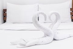 Swans made from towels on the bed Royalty Free Stock Photo