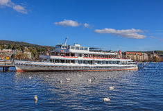Swans and MS Linth at a pier on Lake Zurich Stock Photos