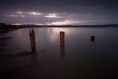 Swansea zatoki groynes przy nocą Fotografia Stock