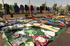 Swap meet with clothes hung on fence