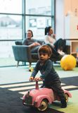 Toddler on pink car. Swarzedz, Poland - January 13, 2019: Toddler boy sitting on a pink toy car next to a zebra crossing in a Hola indoor playground royalty free stock images