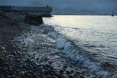 Swash för havsvattenvåg under blå timme arkivbilder