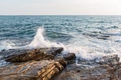 Swashing tegen de overzeese rotsen stock fotografie
