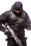 SWAT officer with assault rifle in black uniform isolated on white Royalty Free Stock Images