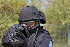Swat police officer pointing a gun at the camera. Close-up Royalty Free Stock Images