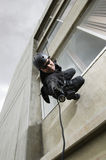 SWAT Team Officer Aiming Gun While Rappelling Royalty Free Stock Image
