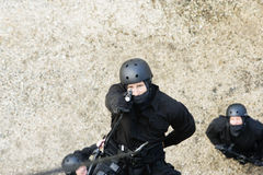SWAT Team Officer Rappelling and Aiming Gun Royalty Free Stock Photos