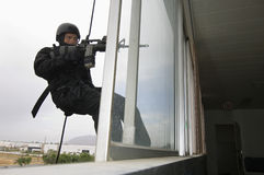 SWAT Team Officer Rappelling And Aiming Gun. Through glass window royalty free stock images