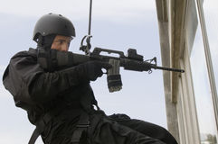 SWAT Team Officer Rappelling and Aiming Gun. Side view of SWAT team officer rappelling and aiming gun through glass window stock image