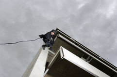 SWAT Team Officer Rappelling and Aiming Gun Royalty Free Stock Photography