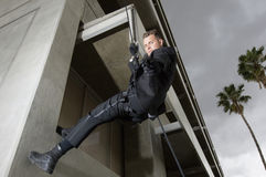 SWAT Team Officer Rappelling and Aiming Gun Royalty Free Stock Images