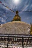 Swayambhunath and prayer wheel under the Halo around the sun , Kathmandu , Nepal ,. Swayambhunath is an ancient religious architecture atop a hill in the stock photography