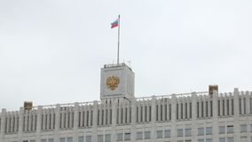 Swaying flag of Russian Federation and crest on top of building in cloudy day. Against sky, close-up view stock footage