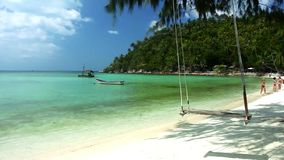Swaying swing on the shore of a tropical island stock footage