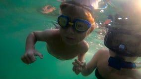 sweaming和潜水在海的妇女和她的儿子的Ultrahd慢动作水下的射击 影视素材
