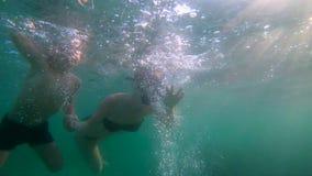 sweaming和潜水在海的妇女和她的儿子的Ultrahd慢动作水下的射击 股票录像