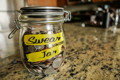 Swear Jar. A clear glass jar filed with coins and bills, saving money. The words Swear Jar written on the outside Royalty Free Stock Photography