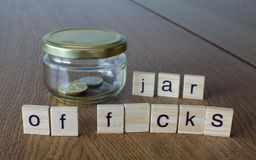 Free Swear Jar `Jar Of F*cks`on The Wooden Table Background. Royalty Free Stock Photo - 142064045