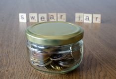 Swear jar on the wooden table background. Letters on wooden blocks stock photo