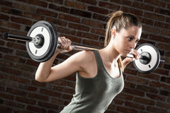 Sweat beautiful girl lifting dumbbells on brick background Stock Photo