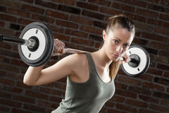Sweat fit woman lifting dumbbells on brick background Royalty Free Stock Images