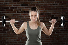Sweat fit woman lifting dumbbells on brick background Stock Photography