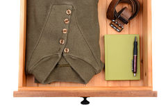 Sweater Drawer. High angle shot of a sweater, belt, book and pen in a dresser drawer. Horizontal format isolated on white stock illustration
