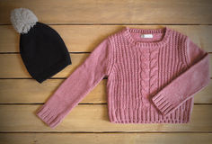 Sweater and hat for baby girl. On wooden background Stock Photos