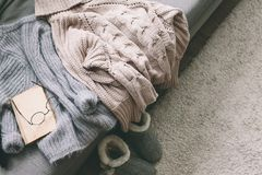 Sweater and reading on sofa. Cashmere sweater and reading on gray sofa. Warm weekend at home. Detail of cozy winter interior Stock Photo