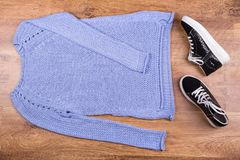 Sweater and sneakers on a laminate. Knitted sweater with sneakers. Trendy autumn look royalty free stock photography