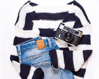 Sweater in white and blue stripes, jeans, and a camera Royalty Free Stock Photos
