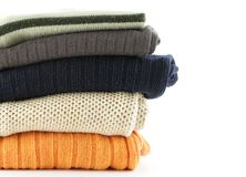 Sweaters. Folded woolen sweaters isolated over a white background stock images