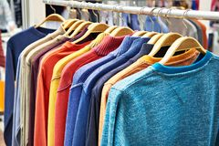 Sweaters on hanger in store Stock Images
