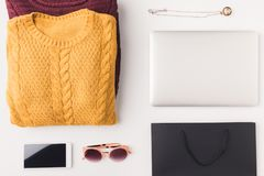 Sweaters, laptop, smartphone and shopping bag. Flat lay with knitted sweaters, sunglasses, pendant, laptop, smartphone and black shopping bag, isolated on white royalty free stock photo