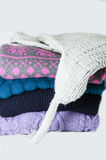 Sweaters stack and woolen hat Stock Photo
