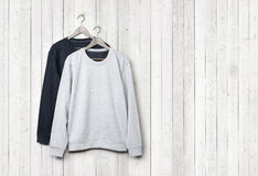 Sweaters on a white wood wall Royalty Free Stock Photo